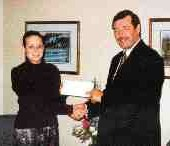 Robert Gow senior vice president Canadian Operations, Lindsey Morden Claims Services Limited, presents the 1998 Colin MacKay Memorial Scholarship to Cynthia Attwood of Mississauga, Ontario. Administered by the Insurance Brokers Association of Ontario, this scholarship is available to students whose parent(s) or guardian is employed by the insurance industry, and who are enrolled in first year studies at college, university or schools of higher learning. The Lindsey Morden scholarship is available in all provinces and territories except Quebec.