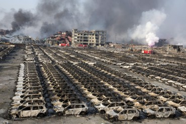 In this Aug. 13, 2015, file photo, smoke billows from the site of an explosion that reduced a parking lot filled with new cars to charred remains at a warehouse in northeastern China's Tianjin municipality. Huge explosions in the warehouse district sent up massive fireballs that turned the night sky into day in the Chinese port city of Tianjin, officials and witnesses said Thursday. (AP Photo/Ng Han Guan, File)