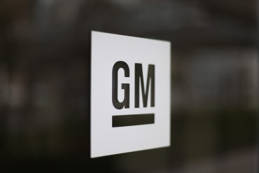 FILE - This Friday, May 16, 2014, file photo, shows the General Motors logo at the company's world headquarters in Detroit. On Friday, April 15, 2016, General Motors is recalling more than a million Chevrolet Silverado and GMC Sierra pickup trucks worldwide because the seat belts may not hold people in a crash. The recall covers certain model 1500 pickups from the 2014 and 2015 model years. GM says a steel cable that connects the belts to the trucks can wear and separate over time. If that happens, the belts could come loose.(AP Photo/Paul Sancya, File)