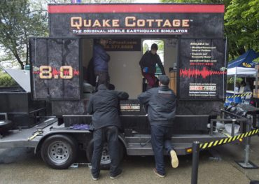 People experience what a earthquake would feel like as they stand inside a earthquake simulator in Vancouver, B.C. Tuesday, May, 5, 2015. THE CANADIAN PRESS/Jonathan Hayward