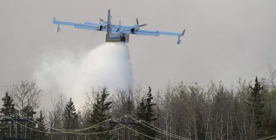 A water bomber drops its load on a wild fire some 16km south of Fort McMurray, Alberta on highway 63 Friday, May 6, 2016. THE CANADIAN PRESS/Jonathan Hayward