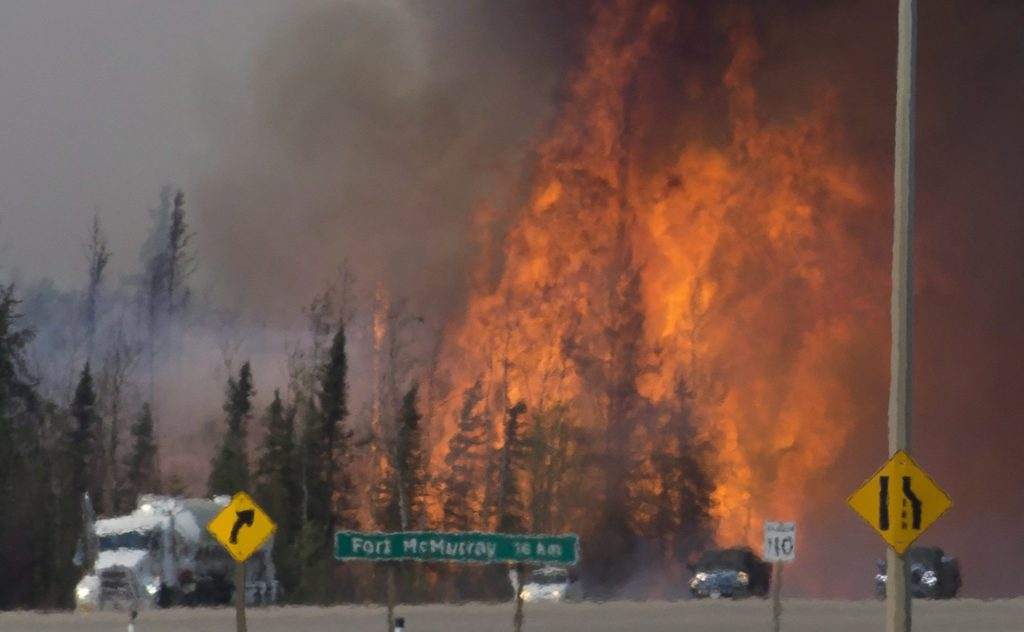 Heat waves are seen as cars and trucks try and get past a wild fire 16km south of Fort McMurray on highway 63 Friday, May 6, 2016. THE CANADIAN PRESS/Jonathan Hayward