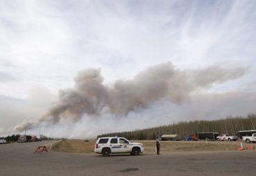 Smoke billows from wildfires as RCMP man a checkpoint on the highway to Fort McMurray, Alberta wildfires that are still burning out of control Saturday, May 7, 2016.THE CANADIAN PRESS/Ryan Remiorz
