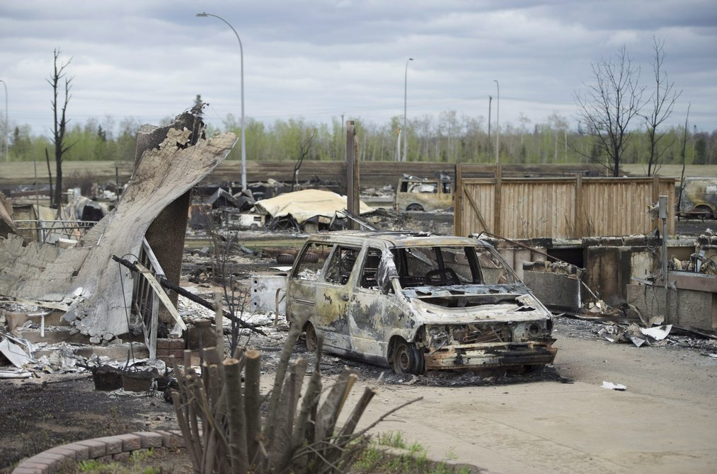 A burnt out van is pictured in the Beacon Hill neighbourhood during a media tour of the fire-damaged city of Fort McMurray, Alta., on Monday, May 9, 2016. THE CANADIAN PRESS/Jonathan Hayward