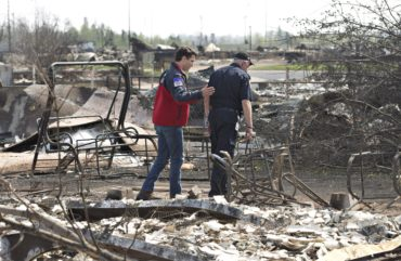 Prime Minister Justin Trudeau, left, and Fort McMurray Fire Chief Darby Allen look over the devastation during a visit to Fort McMurray, Alta., on Friday, May 13, 2016. THE CANADIAN PRESS/Jason Franson