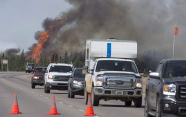 Evacuees drive past a fireball as a wildfire rips through the forest beside Highway 63, some 16 kilometres south of Fort McMurray, Alta. on Saturday, May 7, 2016. Police say a British Columbia man is facing charges for impersonating a Fort McMurray evacuee and allegedly taking advantage of people who were trying to help.THE CANADIAN PRESS/Jonathan Hayward