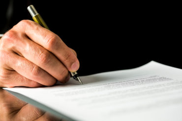 Male hand signing a contract, employment papers, legal document
