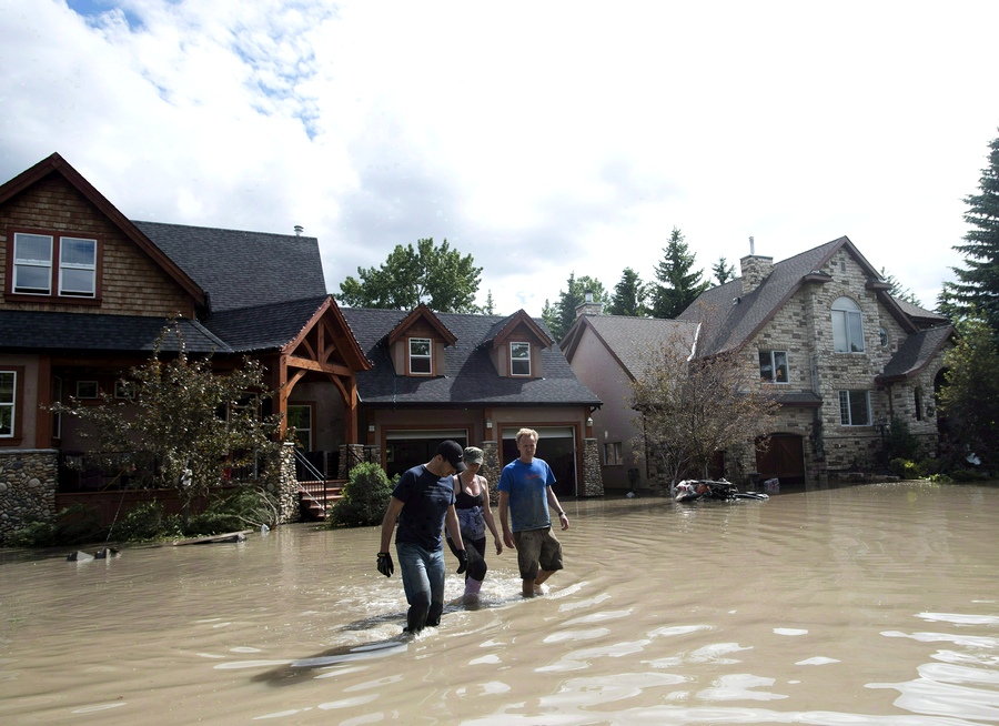 Residents walk through flood waters in Calgary on June 24, 2013. THE CANADIAN PRESS/Nathan Denette