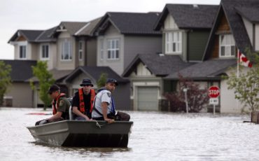 Members of the RCMP return from a boat patrol of a still flooded neighborhood in High River, Alta., on July 4, 2013. After surviving the worst flood in Canadian history a couple of years ago the town of High River, south of Calgary, is holding a mock emergency training exercise this week that shies as far away from water as you can get. THE CANADIAN PRESS/Jeff McIntosh