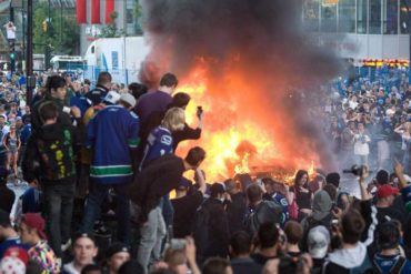 Vancouver Canucks fans watch a car burn during a riot following game 7 of the NHL Stanley Cup final in downtown Vancouver, B.C., on June 15, 2011. Prosecutions for crimes that took place during the 2011 Stanley Cup riots have come to a close, with two more men sentenced to time behind bars. Both William Fisher and Jeffrey Milne were found guilty on a series of charges including aggravated assault, taking part in a riot, and break and enter. THE CANADIAN PRESS/Geoff Howe