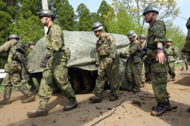 Army troops carry at least one body dug up from a mudslide in Minamiaso, Kumamoto prefecture, Japan Tuesday, April 19, 2016. Searchers digging in a mountainous area of southern Japan where twin earthquakes triggered landslides found another body Tuesday. (AP Photo/Mari Yamaguchi)