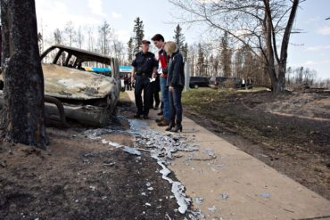 Fort McMurray Fire Chief Darby Allen, left to right, Prime Minister Justin Trudeau and Alberta Premier Rachel Notley look over a burnt out car during a visit to Fort McMurray, Alta., on Friday, May 13, 2016. THE CANADIAN PRESS/Jason Franson