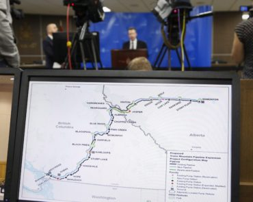 A map of the Kinder Morgan Trans Mountain pipeline is seen in the foreground as Dr. Robert Steedman, Chief Environment Officer of the National Energy Board, centre, releases their report on the Trans Mountain pipeline expansion project are seen in Calgary, Thursday, May 19, 2016.THE CANADIAN PRESS/Jeff McIntosh