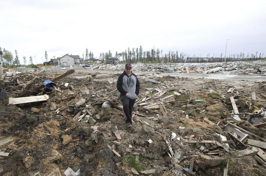 Resident Kenny Gibbons looks through his demolished backyard in the neighbourhood of Timberlea, in Fort McMurray, Alta, on Wednesday June 1, 2016. Residents began returning to their homes after being evacuated due to wildfires. THE CANADIAN PRESS/Jason Franson
