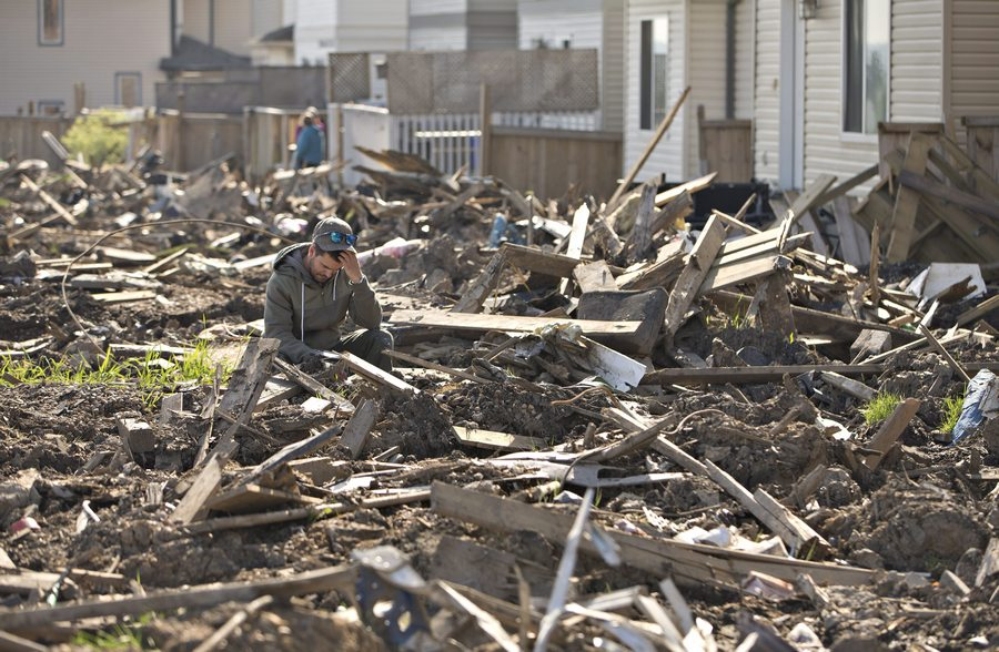 A resident of the Timberlea neighbourhood sits amoung the rubble in Fort McMurray, Alta, on Thursday June 2, 2016. Residents are slowly being allowed back into their homes. THE CANADIAN PRESS/Jason Franson