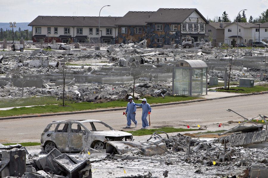 Workers put out markers around a devastated area of Timberlea in Fort McMurray Alta, on Thursday, June 2, 2016. Members of the community are slowly being allowed back into their homes. THE CANADIAN PRESS/Jason Franson