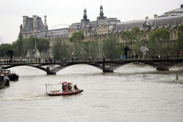 With the Louvre museum in the background, Firemen patrol the flooding Seine river in Paris, France Friday June 3, 2016. Both the Louvre and Orsay museums were closed as the Seine, which officials said was at its highest level in nearly 35 years, was expected to peak sometime later Friday. (AP Photo/Jerome Delay)