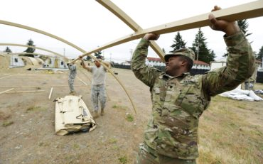 In this photo taken May 24, 2016, U.S. Army Spc. Dedric Bryant, right, of Fort Eustis in Newport News, Va., works to assemble temporary living structures at Joint Base Lewis-McChord in Washington state that will be used by troops taking part in a massive earthquake and tsunami readiness drill overseen by the Federal Emergency Management Agency on June 7-10, 2016. (AP Photo/Ted S. Warren)