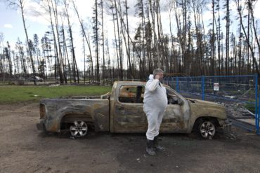 Wade Wilson talks on the phone by his burnt up truck at his home in Saprae Creek near Fort McMurray Alta., on Friday June 3, 2016. Members of the community are now being allowed back into their homes. THE CANADIAN PRESS/Jason Franson