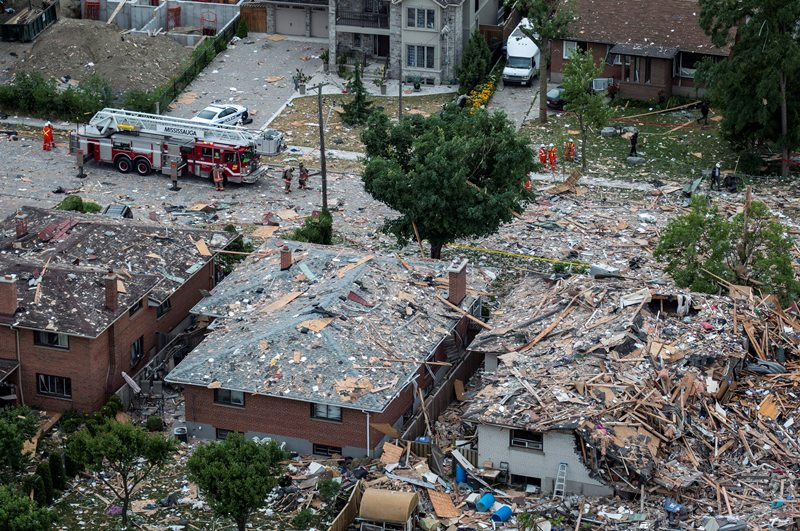 Firefighters examine debris after a house explosion in Mississauga, Ont., Tuesday, June 28, 2016. THE CANADIAN PRESS/Eduardo Lima.