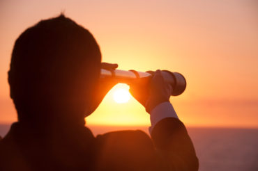 Businessman looking to the future with telescope at sunrise. He is holding the telescope to his eye and looing to the horizon over the ocean. This is a forecasting, discovery, visionary concept. It could also portray surveillance, opportunity, exploration and innovation.