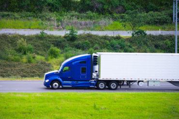 Modern dark blue semi truck reefer trailer profile on road