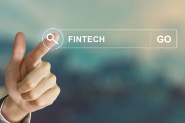 business hand clicking fintech or financial technology button