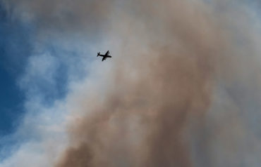 A firefighting plane navigates through smoke from a wildfire burning at Burns Bog in Delta, British Columbia on Sunday, July 3, 2016. Photo by Darryl Dyck, The Canadian Press