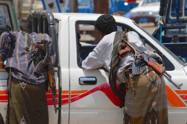 Yemeni people with Kalashnikov guns talk to a car driver.