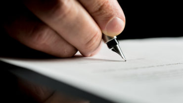Hand of a businessman signing or writing document