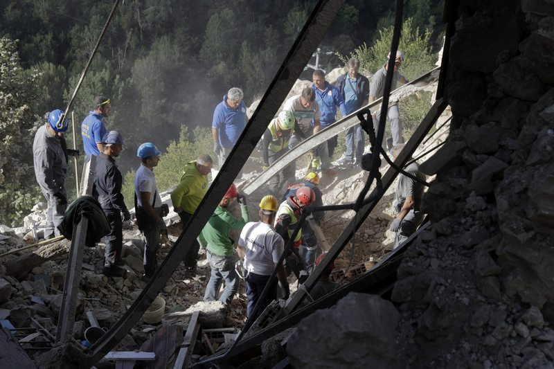Rescuers search for survivors through rubble after an earthquake, in Accumoli, central Italy, Wednesday, Aug. 24, 2016. A devastating earthquake rocked central Italy early Wednesday, collapsing homes on top of residents as they slept. At least 23 people were reported dead in three hard-hit towns where rescue crews raced to dig survivors out of the rubble, but the toll was expected to rise as crews reached homes in more remote hamlets. (AP Photo/Andrew Medichini)