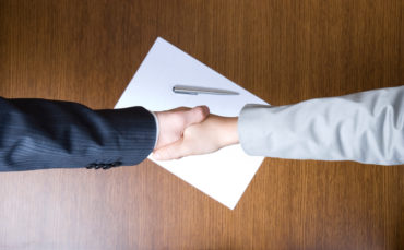 Two businessmen shaking hands over a contract
