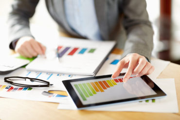 Businesswoman preparing profit report on digital tablet