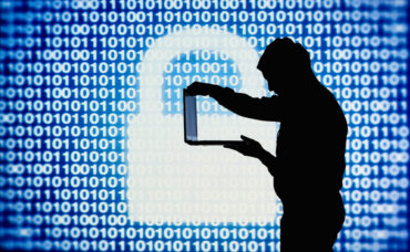 Computer hacker in action with laptop