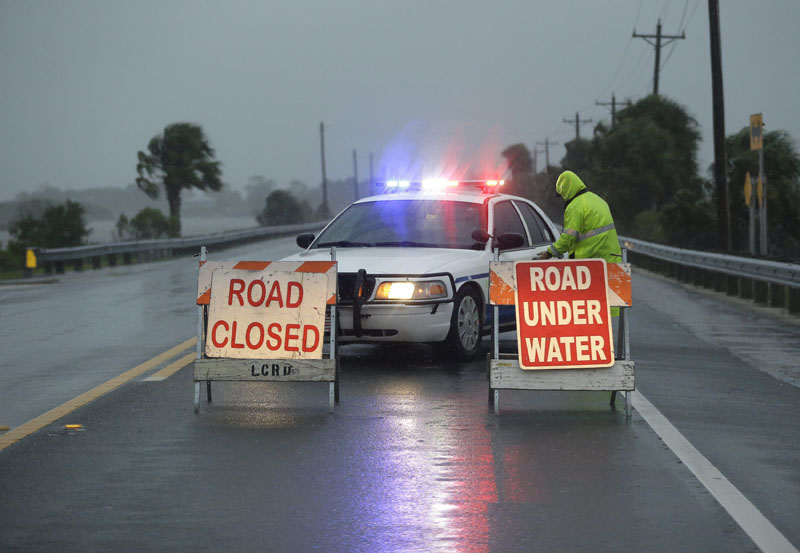 Police block the road entering Cedar Key, Florida, as Hurricane Hermine nears the Florida coast. Hurricane Hermine gained new strength Thursday evening and roared ever closer to Florida's Gulf Coast, where rough surf began smashing against docks and boathouses and people braced for the first direct hit on the state from a hurricane in over a decade. Photo by John Raoux, The Associated Press.
