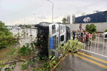 A man rides a scooter past an overturned vehicle and fallen trees after a typhoon in Xiamen in southeastern China's Fujian province Thursday, Sept. 15, 2016. Typhoon Meranti, labeled the strongest storm so far this year by Chinese and Taiwanese weather authorities, made landfall in southeastern China early Thursday after previously affecting Taiwan. (Chinatopix via AP)