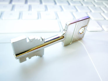 Security key on white laptop close up