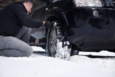 Man installing snow chains.