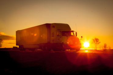 Tractor trailer driving down the highway at sunrise.