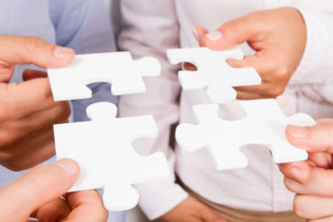 Business teamwork concept with puzzle pieces. Close-up shooting hands of business people which is holding jigsaw puzzle in office.