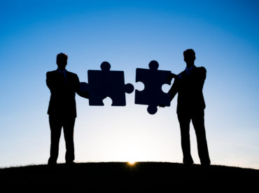 Two Businessmen holding the jigsaw puzzle