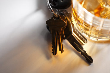 Set of keys sitting at base of glass of alcohol