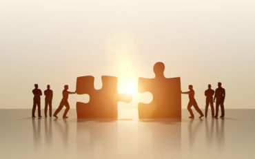 Silhouette of business men merging and solving puzzle