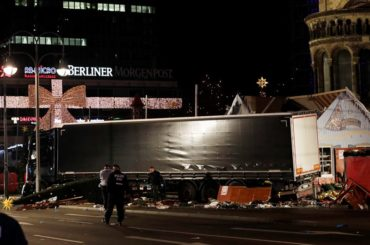 Police officers stand beside a truck which ran into a crowded Christmas market and killed several people in Berlin, Germany, Monday, Dec. 19, 2016. (AP Photo/Michael Sohn)