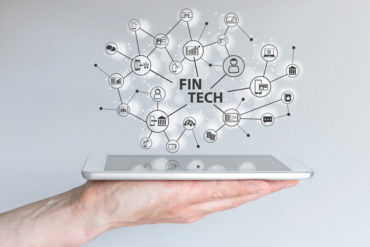 Fin Tech and mobile computing concept. Hand holding tablet