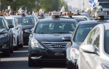 Taxi cabs block a street during a demonstration opposing the presence of Uber in the province of Quebec, in Montreal on Wednesday, October 5, 2016. THE CANADIAN PRESS/Graham Hughes