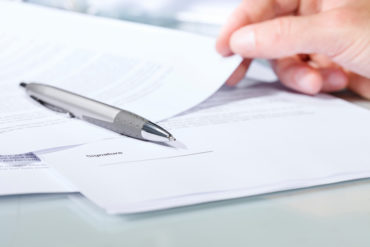 Close-up of a silver pen with documents.