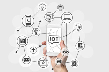 Internet of Things (IOT) concept with hand holding smart phone