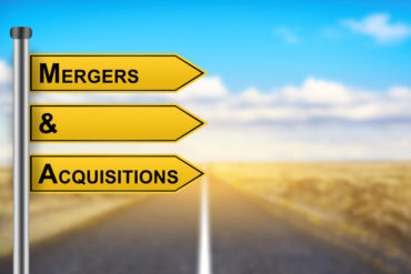 M&A or Mergers and Acquisitions words on yellow road sign