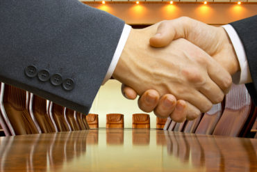 Close-up of a business deal handshake at an empty table